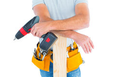 Midsection of male carpenter with power drill and plank Royalty Free Stock Photo