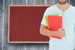 Midsection of male college student holding books while standing against notice board. Digital composite of Midsection of male college student holding books while Stock Images