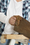 Midsection of male construction worker cutting wood with handsaw Stock Image