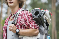 Midsection of male hiker carrying backpack in forest Stock Image