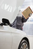Midsection of male maintenance engineer repairing car in automobile store Stock Photography