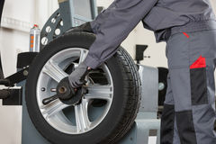 Midsection of male mechanic repairing car's wheel in repair shop Stock Photos