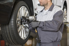 Midsection of male mechanic repairing car's wheel in workshop Royalty Free Stock Photography