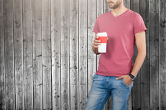 Composite image of midsection of male model holding disposable cup. Midsection of male model holding disposable cup against wooden planks background Stock Photography