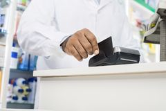 Midsection Of Pharmacist Swiping Credit Card On Reader. Midsection of male pharmacist swiping credit card on reader in pharmacy Stock Images