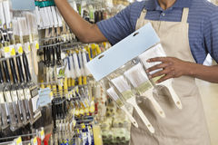 Midsection of male store clerk holding painting tools Royalty Free Stock Photography
