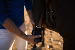 Midsection of male trainer adjusting woman leg on stirrup Royalty Free Stock Photo