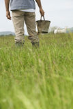 Midsection Of Man With Bucket In Field Stock Images