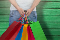 Composite image of midsection of man carrying colorful shopping bag against white background Stock Photography