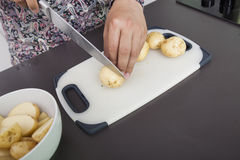 Midsection of man cutting potato at kitchen counter Stock Image