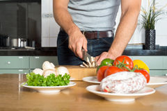 Midsection Of Man Cutting Vegetables At Kitchen Co Royalty Free Stock Images
