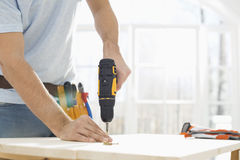Midsection of man drilling nail on table Stock Images