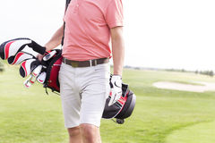 Midsection of man with golf club bag standing at course Stock Image