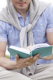 Midsection of man holding book in park Royalty Free Stock Image