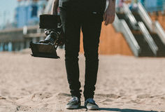 Midsection of Man Holding a Camera Standing in the beach Royalty Free Stock Photography