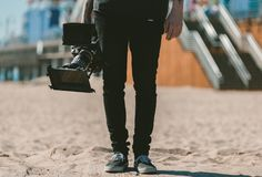 Midsection of Man Holding a Camera Standing in the beach Stock Photo