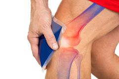 Midsection Of Man Holding Cool Gel Pack On Knee. For pain relief over white background stock image