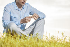 Midsection of man holding flower while sitting on grass against clear sky Stock Image