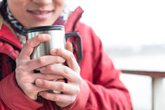 Midsection of man holding insulated drink container during winter Royalty Free Stock Photography