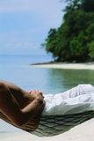 Midsection of man lying in hammock at beach.  royalty free stock photography