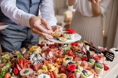 Midsection of a man putting food on plate on a indoor family birthday party. Midsection of a man putting food on a plate on a indoor family birthday party stock photos