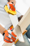 Midsection of man sawing plank Royalty Free Stock Photos