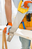 Midsection of man sawing wood in new house Royalty Free Stock Photography