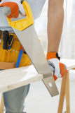 Midsection of man sawing wood in new house Royalty Free Stock Images