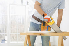 Midsection of man sawing wood in new house Stock Photography