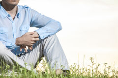 Midsection of man sitting on grass against clear sky Stock Photography