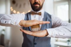 Midsection of man standing indoors in a room set for a party, holding a beard comb. A midsection of man standing indoors in a room set for a party, holding a stock photo