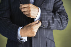 Midsection Of Man In Suit Buttoning Cuff Sleeves. Closeup midsection of a businessman in suit buttoning cuff sleeves stock photos