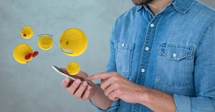 Midsection of man using smart phone while emojis coming out from it Royalty Free Stock Photos