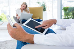 Midsection of man using tablet while woman holding laptop. Midsection of men using tablet while women holding laptop at home stock photography