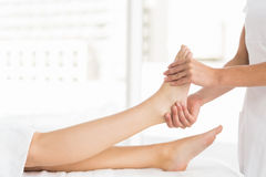 Midsection of masseur giving foot massage to woman Stock Photo