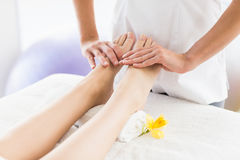Midsection of masseur giving foot massage to woman Royalty Free Stock Image