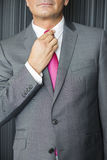 Midsection of mature businessman adjusting necktie Royalty Free Stock Photos