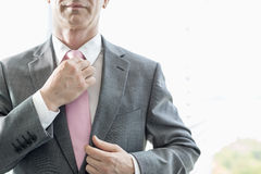 Midsection of mature businessman adjusting necktie Stock Images