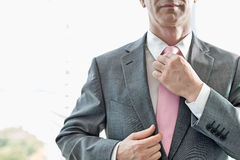 Midsection of mature businessman adjusting necktie Stock Photos