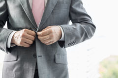 Midsection of mature businessman buttoning his blazer Royalty Free Stock Photos