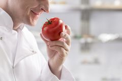 Midsection of mature chef smelling fresh red tomato while standing at restaurant kitchen stock photography