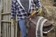 Midsection of a mature man holding horse riding tack Stock Photos