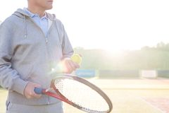 Midsection of mature man holding tennis balls and racket on court against clear sky royalty free stock images