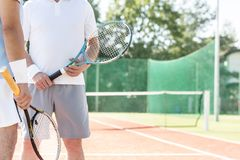 Midsection of mature men holding rackets while standing on tennis court during summer weekend stock images