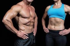 Midsection mięśniowy mężczyzna i kobieta z rękami na biodrze Zdjęcie Stock