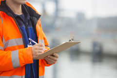 Midsection of mid adult man writing on clipboard in shipping yard Royalty Free Stock Images