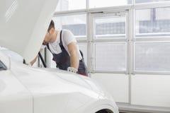 Midsection naprawia samochodowego silnika w warsztacie męski technik Obraz Royalty Free