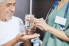 Midsection Of Nurse Giving Medicine And Water To Patient. Midsection of nurse giving medicine and water to smiling male patient in rehab center stock photo