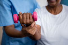 Midsection of nurse guiding senior woman in lifting dumbbell Stock Photography