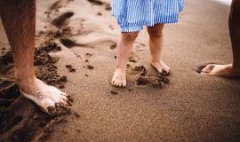 A midsection of parents with toddler daughter stabding on beach on summer holiday. A midsection of parents with toddler daughter standing on beach on summer royalty free stock images